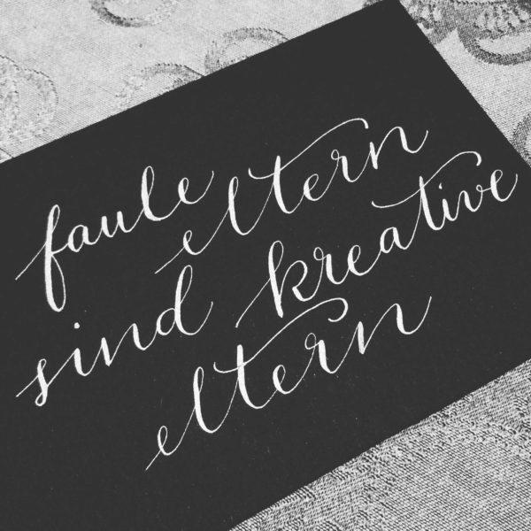 Kalligrafie mit weißer Tinte auf schwarzem Papier